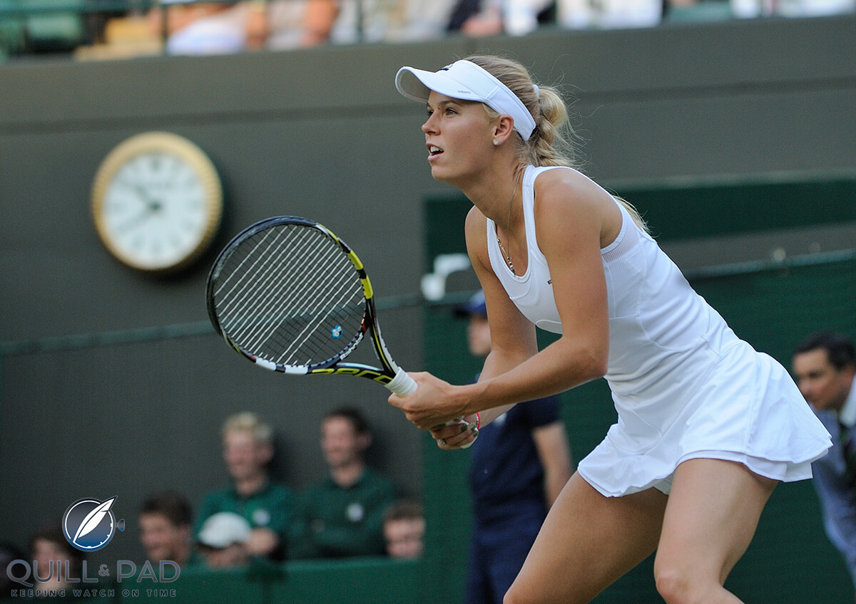 World number 5 Caroline Wozniacki playing at Wimbledon; note the Rolex clock in the background